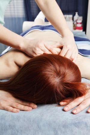 Redhead woman laying down on couch having shoulder massage Stock Photo - 18602206