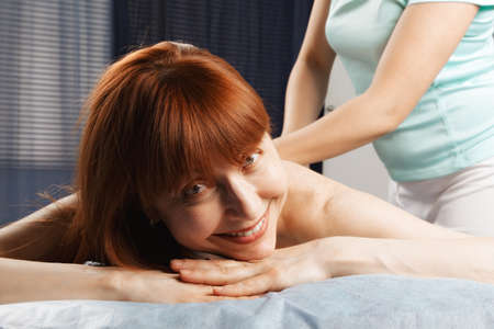 Positive middle-aged caucasian redhead woman having a massage Stock Photo - 18602195