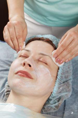 Massagist removing massage cream from caucasian woman face Stock Photo - 18602189
