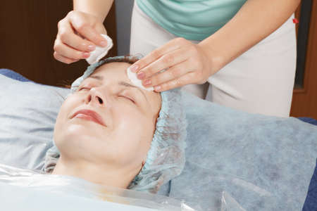 Masseur removing massage cream from caucasian woman face Stock Photo - 18602198