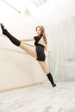 barre: Young caucasian brunette woman stretching up on barre Stock Photo