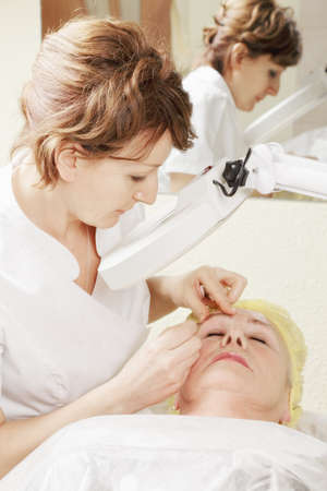 Beautician does eyebrows tweezing procedure for senior woman photo