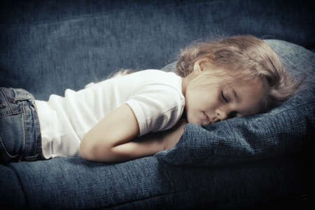Little caucasian girl sleeping on the blue sofa