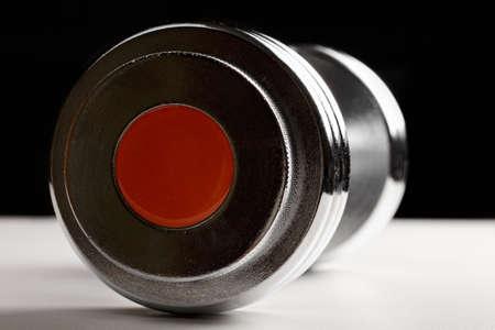 adjustable dumbbell: Adjustable dumbbell on white surface against dark background Stock Photo