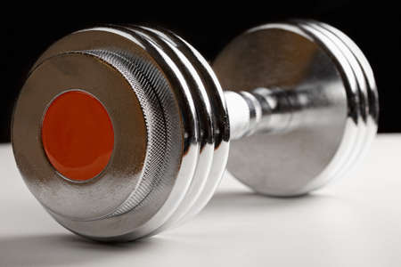 adjustable dumbbell: Adjustable dumbbell against dark background closeup photo