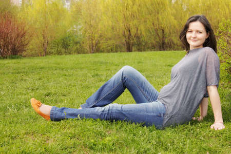regnant: Contented young regnant woman sitting on the grass in park Stock Photo