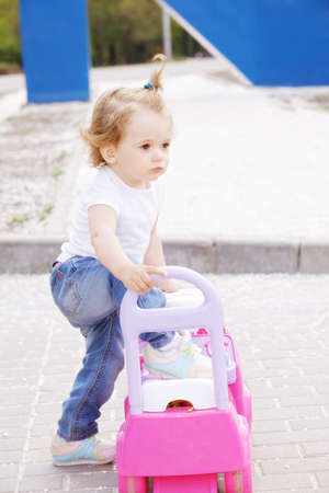 Little blonde caucasian girl with pink toy car in a park photo
