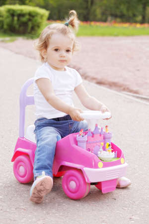 Little blonde caucasian girl riding pink toy car in a park photo