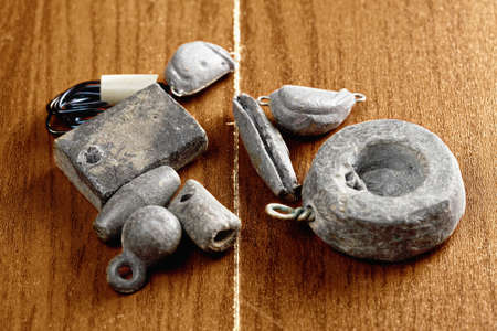 sinkers: Various lead sinkers on a wooden surface