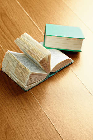 books on a wooden surface: Open and closed green old books over wooden surface