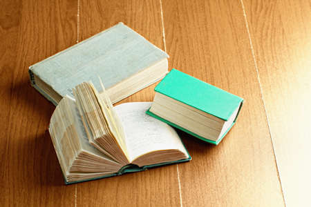 books on a wooden surface: Three old books over wooden surface