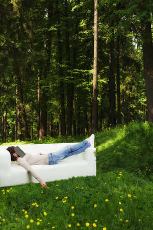 Young woman having nap in green forest on a white sofa Stock Photo - 21171468