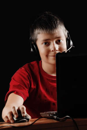 Teen boy with laptop sitting at the desk in darkness photo