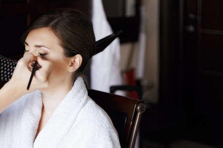 eyelid: Beautician applying eye shadow to eyelid of woman in bathrobe