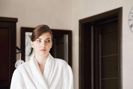 looking sideways: Serious young woman in bathrobe looking sideways