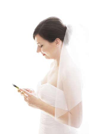 Bride with cellphone profile view against white background photo