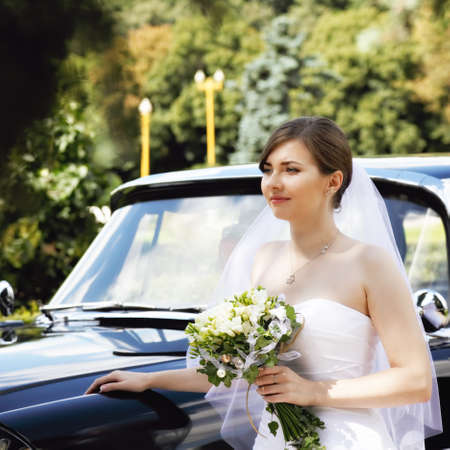 looking sideways: Bride with flowers standing at the car and looking sideways Stock Photo