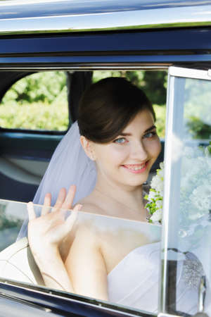Cheerful bride sitting in the old car photo