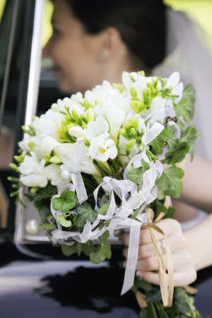 Bunch of flowers in the hand of bride sitting in car photo