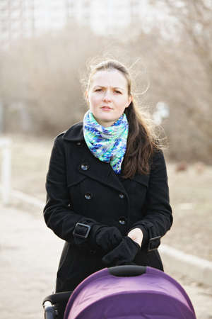 parentage: Young woman in black coat standing with stroller outdoors and wearing on gloves