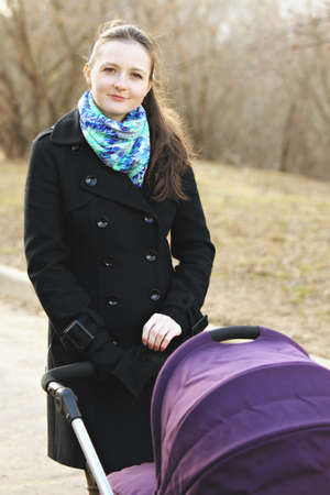 Young woman walking with stroller in a park Stock Photo - 27345532