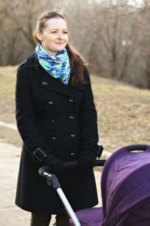 Positive young woman with stroller looking sideways photo