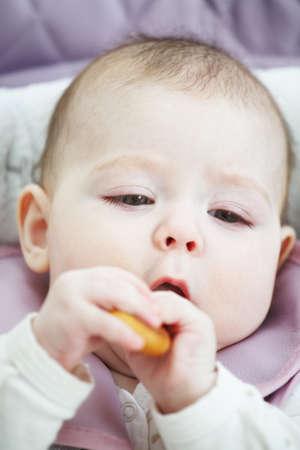 looking sideways: Baby eating bagel looking sideways