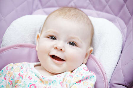 child seat: Smiling baby in a child seat closeup portrait