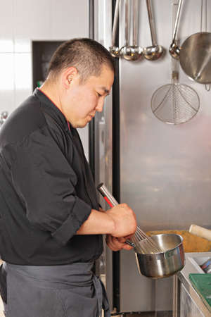 weighs: Chef mixing ingredients in pan at the kitchen
