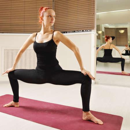 looking sideways: Redhead in standing yoga pose looking sideways Stock Photo
