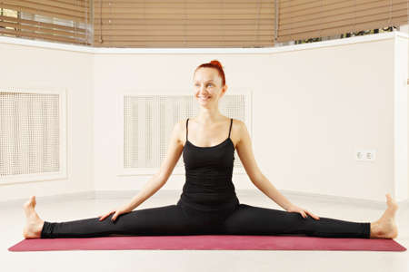 contented: Contented redhead stretching legs out yoga pose Stock Photo