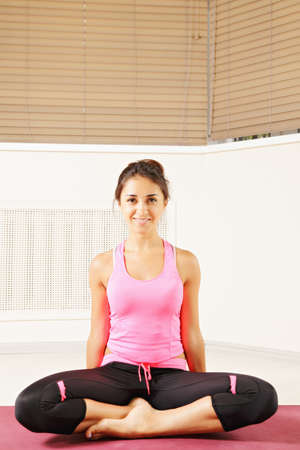 pleasant emotions: Smiling brunette woman sitting on a mat legs folded