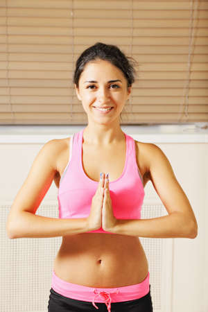 pleasant emotions: Cute young brunette woman at gym standing palms folded