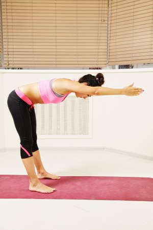 bending forward: Young brunette woman bending forward while exercising yoga in gym