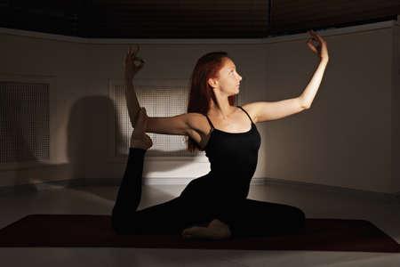 hatha: Redhead woman exercising hatha yoga in a dark gym
