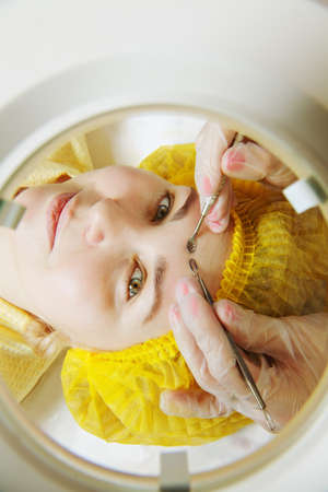 threading hair: Woman at face epilation gaze through magnifying glass