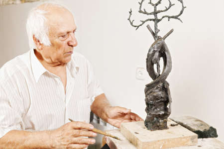 Sculptor looking at his work in a workshop photo