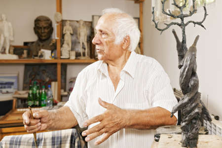 Sculptor near his work at the workshop looking sideways and gesticulating photo