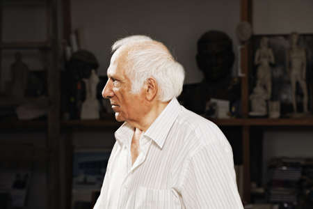 Serious elderly sculptor in dark workshop looking sideways photo