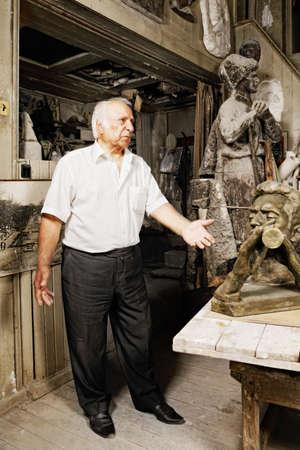Elderly man standing in sculptor workshop photo