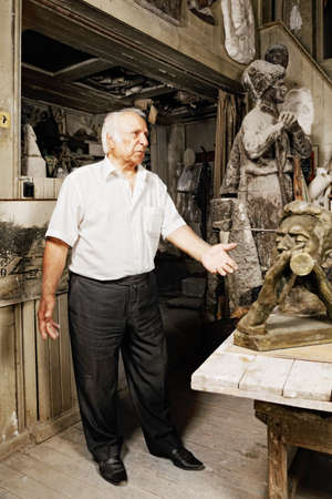 Elderly man standing in sculptor workshop photo