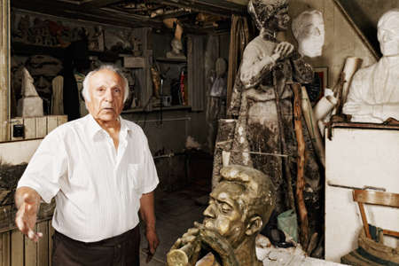 Man among sculptures in a workshop photo