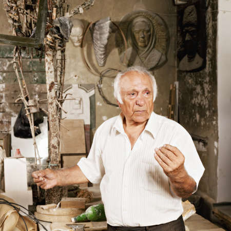 Expressive man gesturing while standing at sculptor workshop photo