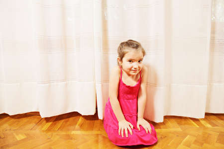 pleasant emotions: Little girl in red dress sitting on the floor