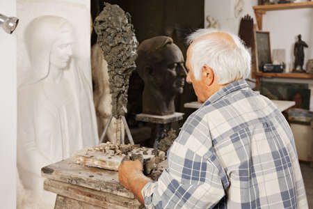sculptor: Sculptor standing at his new work in a workshop
