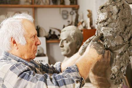 Sculptor works on sculpture nose at studio photo
