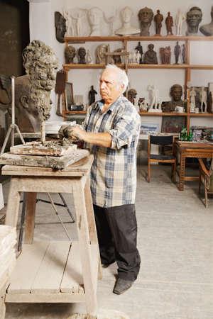 Elderly sculptor creates head in a studio photo