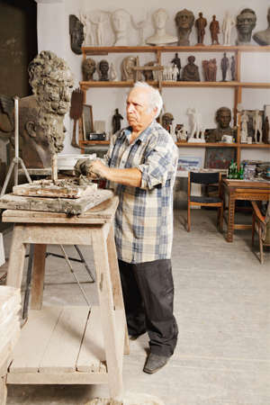 creates: Elderly sculptor creates head in a studio