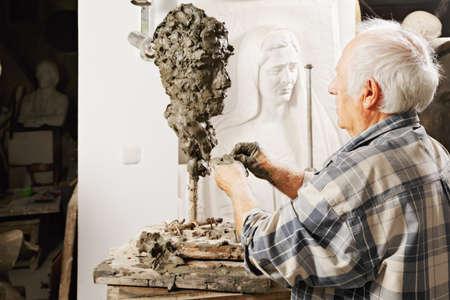 sculptor: Elderly sculptor making sculpture profile view Stock Photo