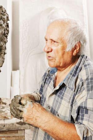 Portrait of elderly sculptor in studio photo